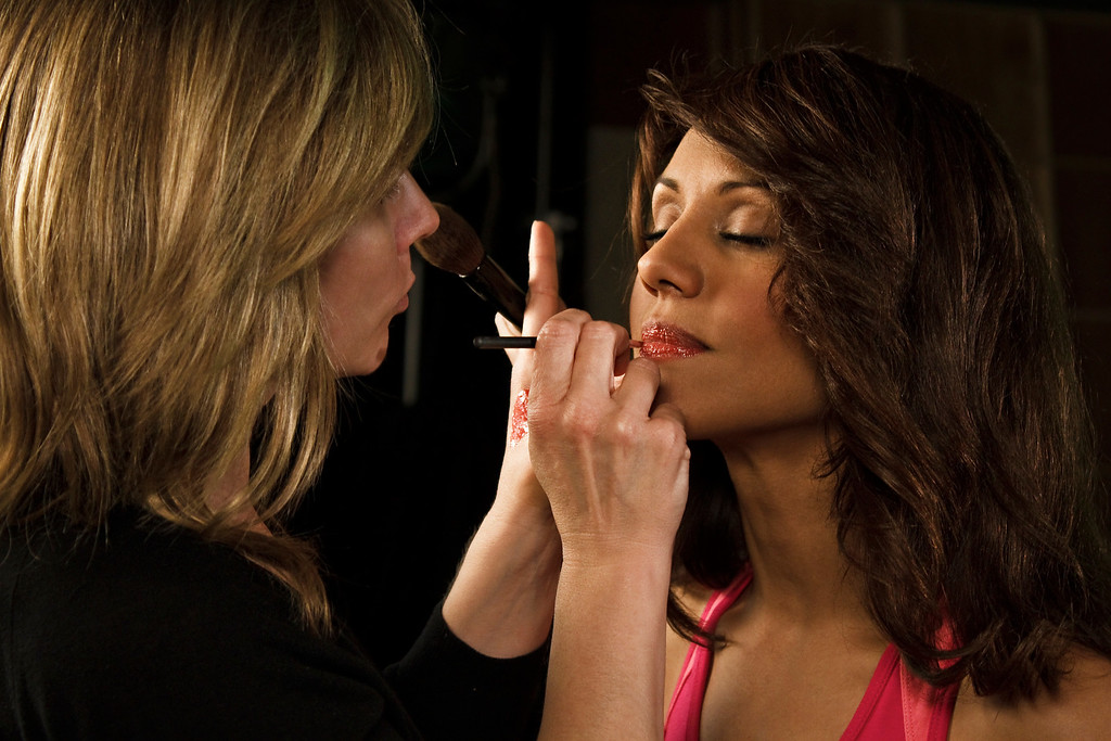 Tara (makeup artist) touches up Evelyn's lips before the next scene.