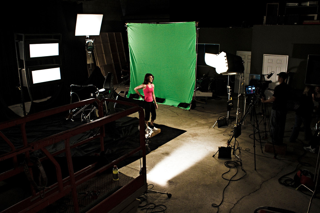 """Evelyn is standing in for a lighting check and practicing some lines. She is switching on the """"ear prompter"""" tape recorder/player located at the back of her waist."""