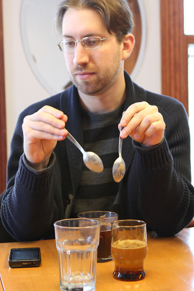 Two spoons, moving in a semi circle (one clockwise, one counterclockwise) can clear the grounds from the top of the coffee in two or three attempts.  Spoons are rinsed and then used for tasting.