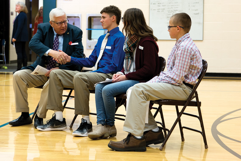 Matthew Gaston | The Sheridan Press<br>U.S. Senator Mike Enzi, left, introduces himself to Tongue River Middle School student Dawson Richards, left center, before the start of the Veterans Day Assembly Thursday, Nov. 8, 2018.