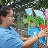 "Volunteer Samantha Diaz, of Leominster, works on the unify Fitchburg art puzzle project at the ""Juneneenth Celebration"" at Riverfront Park in Fitchburg on Saturday afternoon. SENTINEL & ENTERPRISE / Ashley Green"