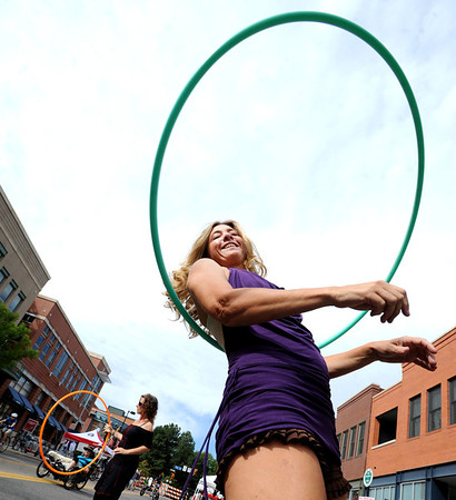 """Kristina Sutcliffe of O Dance, works the hula hoop with  Dena Nishek, in the background, during the Boulder Ciclovia on Pearl Street.<br /> Boulder Green Streets and the City of Boulder  put on the third annual Boulder Ciclovia on Sunday.<br /> For more photos and a video of the Boulder Ciclovia, go to  <a href=""""http://www.dailycamera.com"""">http://www.dailycamera.com</a>.<br /> Cliff Grassmick  / September 16, 2012"""