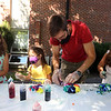 Lawrence Library in Pepperell hosts a socially-distanced tie-dye event, sponsored by Friends of the Lawrence Library. Eloi Jacinto of Pepperell and daughters, from left, Iyla, 7, Sabrina, 4, and Viviana, 8, color their shirts.  (SUN/Julia Malakie)
