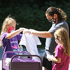 Lawrence Library in Pepperell hosts a socially-distanced tie-dye event, sponsored by Friends of the Lawrence Library. From left, Deanna Bourbeau of Pepperell and daughters Kacie, 9, left, and Rylie, 7, pick out their size tee shirts to dye. (SUN/Julia Malakie)