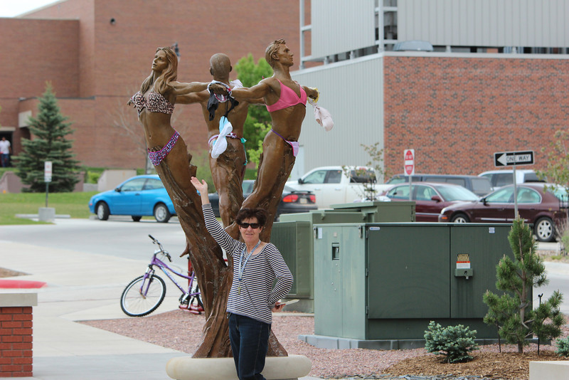 Laure Sinn, CSC student activities coordinator, shows off The Muses and their summer attire. The sculpture between Sparks Hall and Old Admin have become the subject of several pranks since being installed in fall 2011. (Photo by Justin Haag)