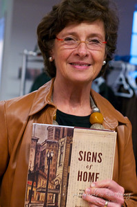 Barbara Johns holding a copy of her new book, Signs of Home: The Paintings and Wartime Diary of Kamekichi Tokita