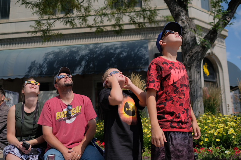 Justin Sheely | The Sheridan Press<br /> The Ruzanski family, from left, Kate, William, Andrew, 9, and William, 12, of Missoula, Montana, watch the sun through their solar viewing glasses during the total solar eclipse Monday, August 21, 2017, in downtown Casper, Wyoming.