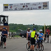 Cyclists gather beneath the banner marking the start and finish of the Tour de Donut prior to heading out on their ride.