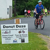 Bicyclists ride past a sign on Route 18 promoting the Tour de Donut and the previous night's Donut Crawl activities in New Wilmington.