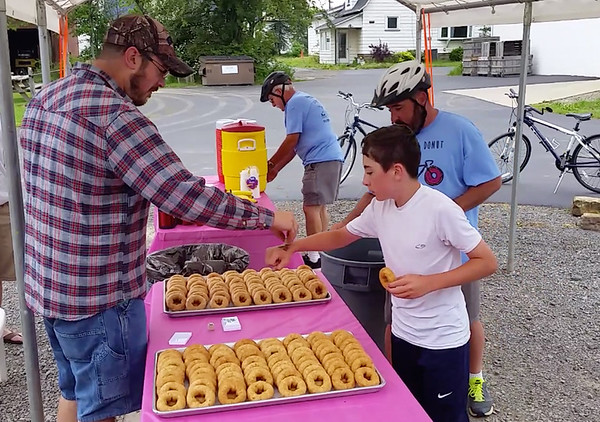 Timmy Pappagallo gets his hand stamped at the Apple Castle donut stop to document that he had eaten one of the bakery treats during the Tour de Donut. Behind him are his father, Tim, and grandfather Wayne Bowen.