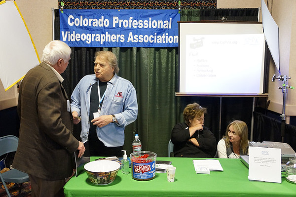Here the camera is held hig to avoid covering the Colorad Professional Videographers Association banner, and positioned to the left so the screen doesn't block the last word.  People engaging is the theme.