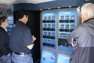Attendees viewing products in a truck outside the show floor.  Here the product wall is primary and the story is of connection with vendor, attendees, and product.  Notice how the frame is filled, cutting off the backs of the men on the ends.  _DSC0956