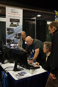 Angle, and composition show product, signage, and interaction.  Exhibitor is surrounded y customers as he demonstrates Broadcast Pix.  Orientation is vertical to include signage. _DSC0612
