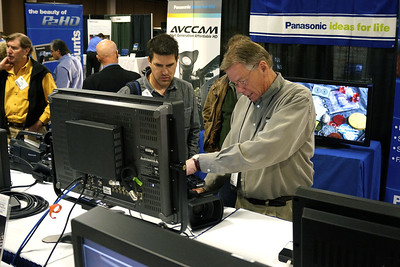 Notice how cropping and composition make the Panasonic name and slogan obvious, as a customer connects with the Panasonic rep.  Additional Panasonic products appear on signs in the background, as do more attendees, all engaged in the show.