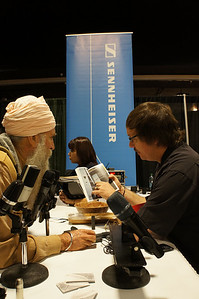 The Sennheiser rep engages a customer at his booth, with Sennheiser microphones in the foreground and the Sennheiser banner in the background.  Antother customer in the background is also engaged.  Orientation and precise camera position allow me to combine the elements in this shot, taken without flash, using available light.  This was not posed.  I visited the booth a number of times, waiting for the right combination to tell this compelling story.  _DSC1387