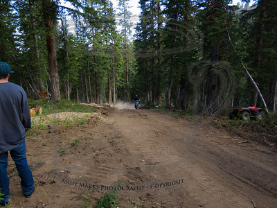 "Day 1, with a trail crew member (Konnor), a few ""rounds"" stashed at roadside, Keith on his Yamaha 250, and a Honda ATV. The new road (dusty, with talc like soil) is also shown. This was early in the morning (8:24) as we were getting straight on just what it was we were there to do."