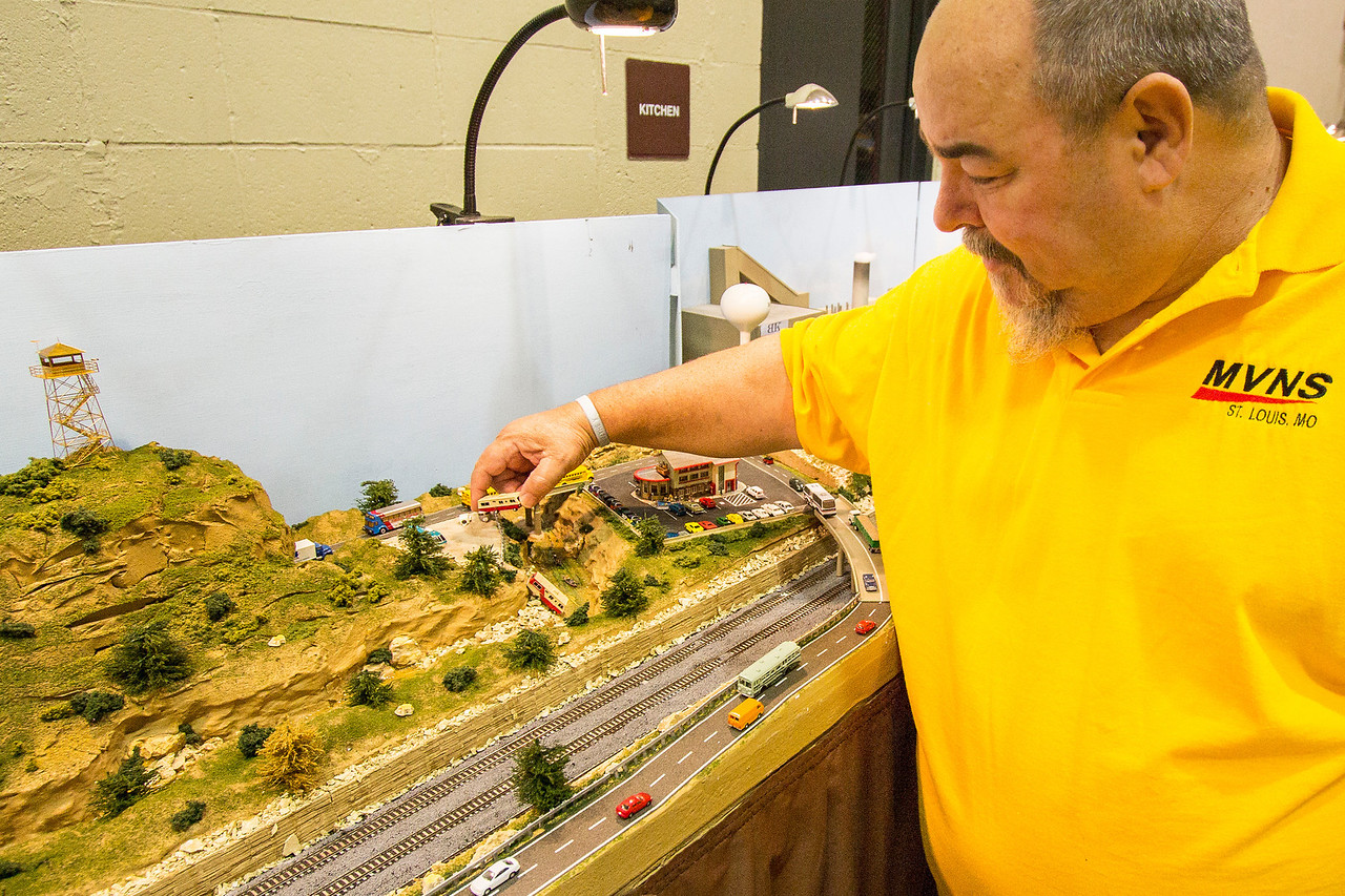 "What makes this N scale layout look so ""real"" is the attention to details. Rocks are hand-carved and cast, trees are made and carefully positioned, even the center lines of the divided highway must be added.  Here a custom cast, hand-painted mobile home is placed in a parking lot by the modeler who created it, Joe Rose of the Mississippi Valley N Scalers (MVNS)."