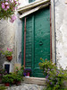 Old green door with its peeling paint in a small Italy village in the hills above Finale - Liguria - Italy