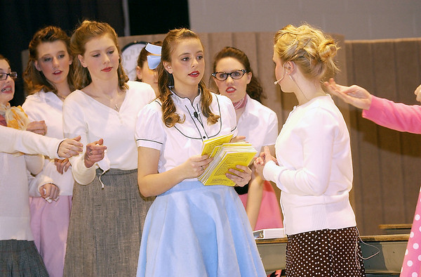"Record-Eagle/Garret Leiva<br /> Kelley Ritsema, as Jane, helps Miss Brooks pass out copies of 'Lost Horizon' to the eager students gathered to audition for a role in the school play in a scene from the Traverse City Christian High School production of ""Our Miss Brooks."""