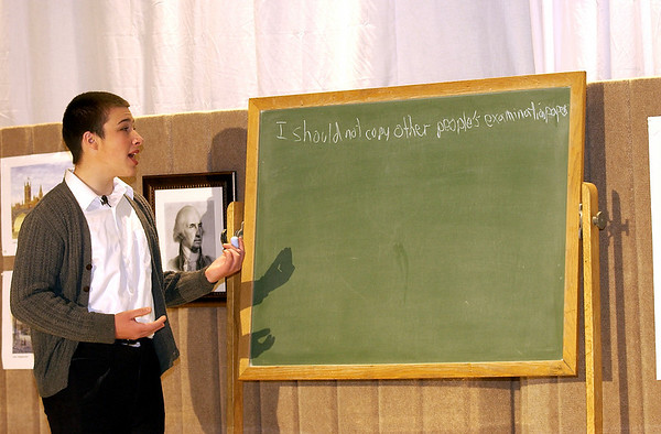 "Record-Eagle/Garret Leiva<br /> Alex Heald, in the role of Ted, writes out his punishment for copying another student's exam in a scene from the Traverse City Christian High School production of ""Our Miss Brooks."""