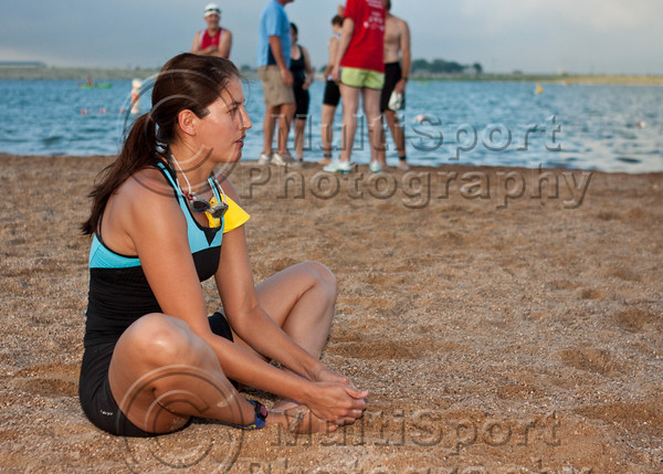 A participant calms herself with some stretching on the beach minutes before her swim start.