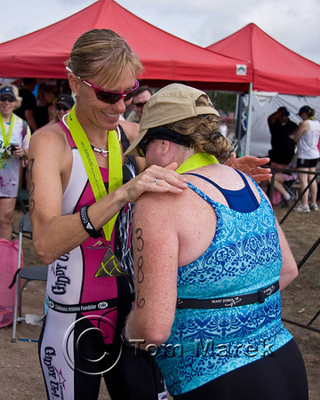 Ironman World Champion and Olympic Silver Medalist Michellie Jones (L) congratulates a finisher at the finish line.