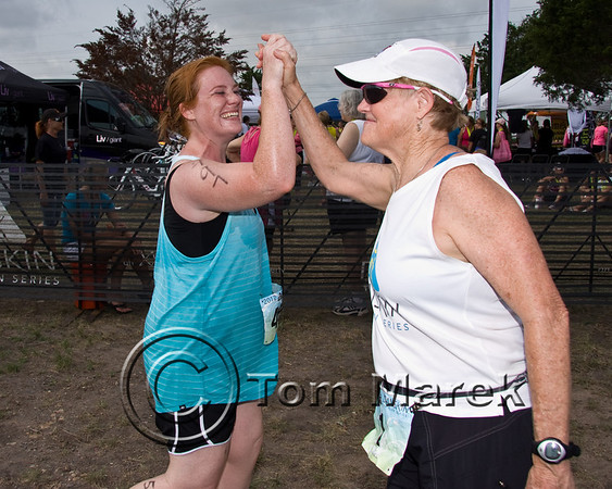 Sally Edwards offers a hi-five and a smile to a finisher about to cross the finish line.