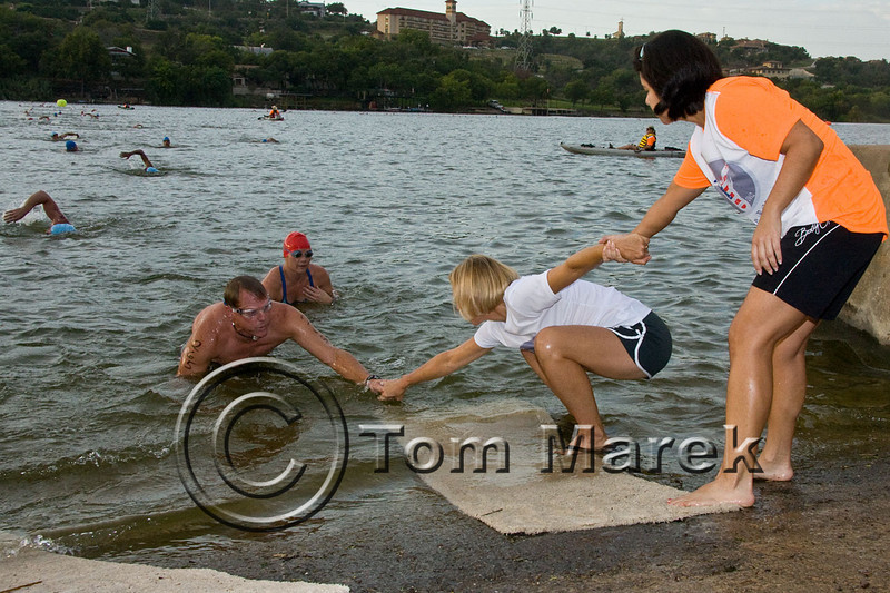 Volunteers form a human chain to help athletes exit the water because of a very slipery boat ramp
