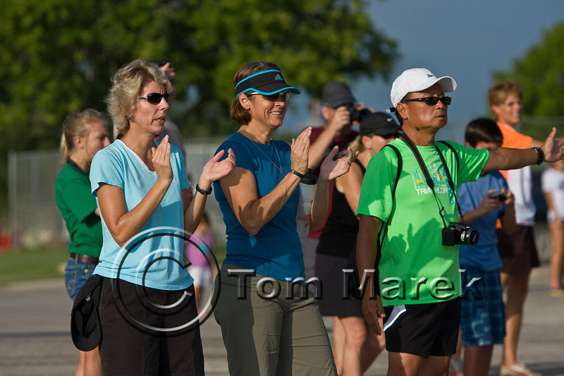 Spectators cheer incomming cyclists as they finish the bike course