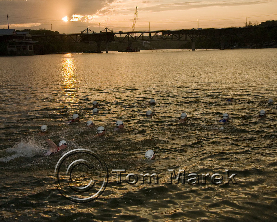 A wave of athletes heads out for their swim