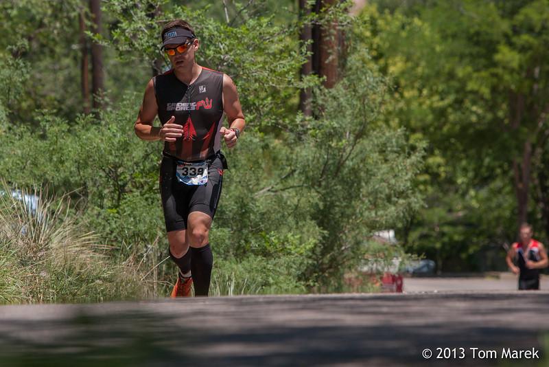Joseph May of Benbrook, TX runs through a tree lined area of the run course.