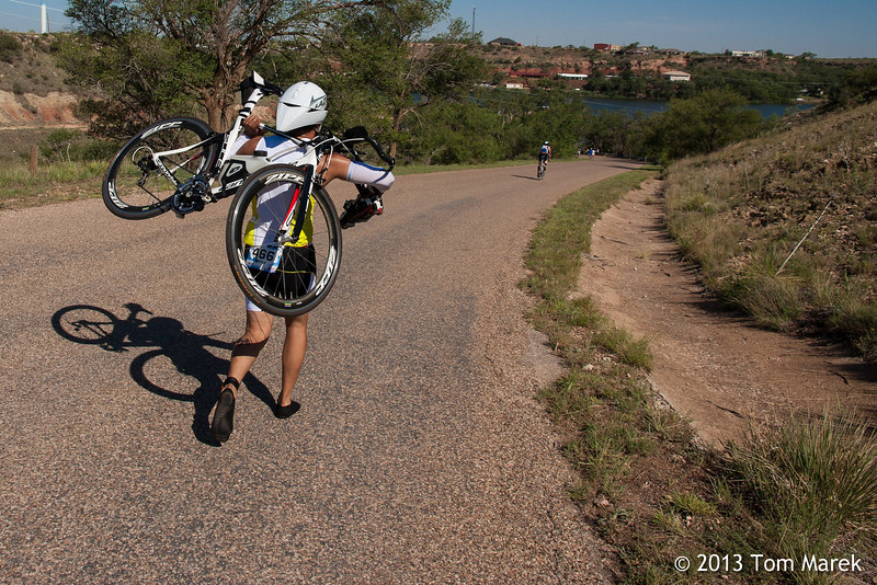George Aranda of Ruidoso, NM carries his bike the last mile of the bike course because of a broken shoe clip.
