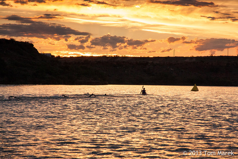 A kayaker helps guide the first swimmers in the early morning light of the Buffalo Springs Lake triathlon.