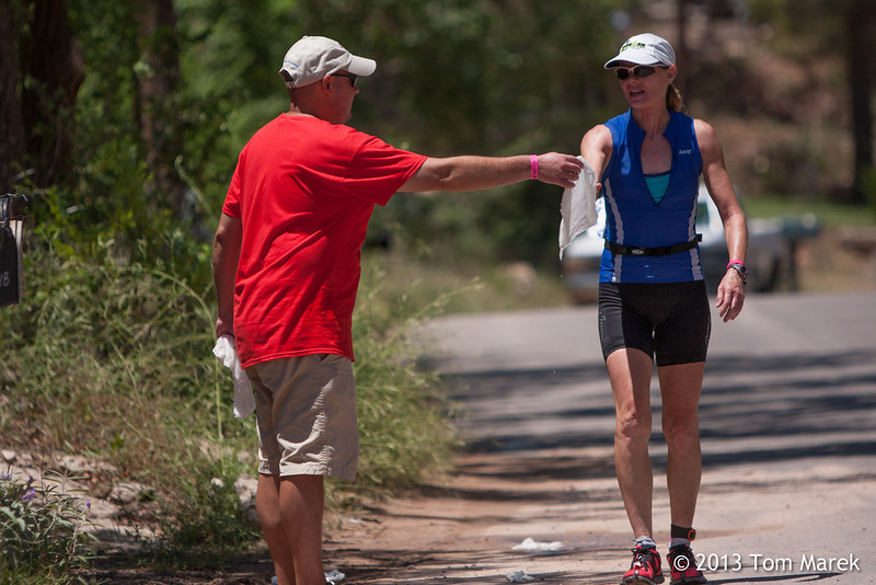 A volunteer gives an athlete a towel soaked in ice water to help her cool down.