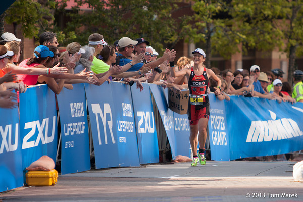 Austinite Jennifer Lentzke (Canada) receives high-fives from spectators as she nears the finish line.