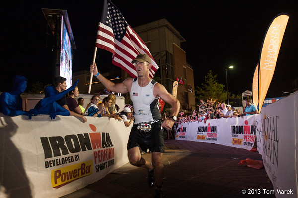 Steve Hinton (Carlesbad, CA) carries the flag toward the finish of Ironman Texas.