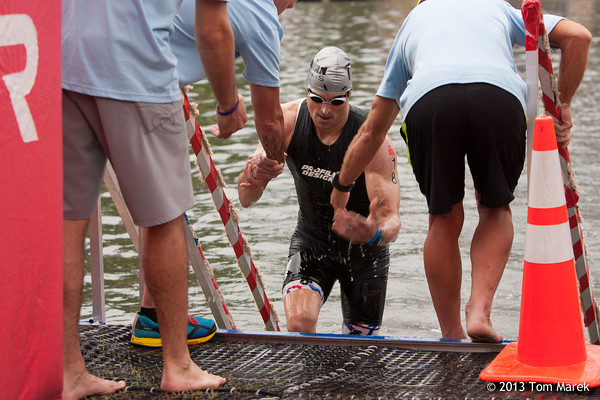 Volunteers help professional triathlete James Lamastra (Rocky River, OH) exit the swim.