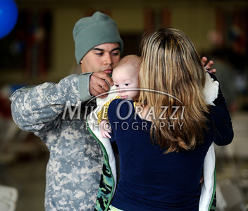 11/17/2010 Mike Orazzi | Staff PFC Hiram Donato wraps his four month old daughter Aiden while she is held by his wife Tanya after he arrived at Bradley Airport with fellow soldiers from the 1st Battalion, 102nd Infantry and Company F, 186th Brigade Support Battalion (BSB) of the Connecticut Army National Guard on a Delta flight Wednesday morning, November 17, 2010 after serving in Afghanistan since January.