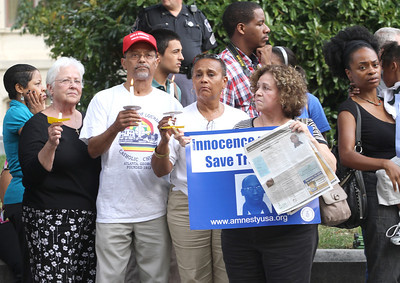 (L-r) Dominican Sister Nora Ryan, holding a candle, Lawrence and Beatrice Soublet of Our Lady of Lourdes Church, Atlanta, and Estela Tabor of Corpus Christi Church, Stone Mountain, stand in protest to Troy Davis' impending execution along Washington Street in front of the Georgia State Capitol.