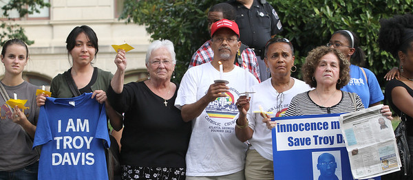(L-r) Jesuit volunteers Kristen Kennedy and Kristina Mata, Dominican Sister Nora Ryan, Lawrence and Beatrice Soublet of Our Lady of Lourdes Church, Atlanta, and Estela Tabor of Corpus Christi Church, Stone Mountain, stand in protest to Troy Davis' impending execution along Washington Street in front of the Georgia State Capitol.