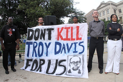 (L-r) John McRae of Atlanta, Georgia State University students Max Fine and Chad Dobler, Michael O'Reilly of Amnesty International, and Rev. Kim Jackson, the Episcopal chaplain at the Atlanta University Center stand among the crowd as speakers prayed and spoke in opposition to the death penalty and the execution of Troy Davis.