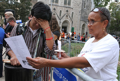 Twenty-year-old Gustavo Madrigal of Griffin, left, and Beatrice Soublet of Our Lady of Lourdes Church, Atlanta, join the protesters in reading the names, in unison, of the 50 men executed in Georgia since the reinstatement of the death penalty in 1976. Hundreds of people joined the Sept. 21 vigil for Troy Anthony Davis.  (Page 11, September 29, issue)