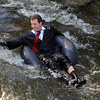 Roy Leckonby, in suit and tie, floats down Boulder Creek as part of tube to work day.<br /> Cliff Grassmick / June 25, 2010