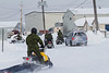 Soldiers on snowmobiles arrive at Moosonee Airport.