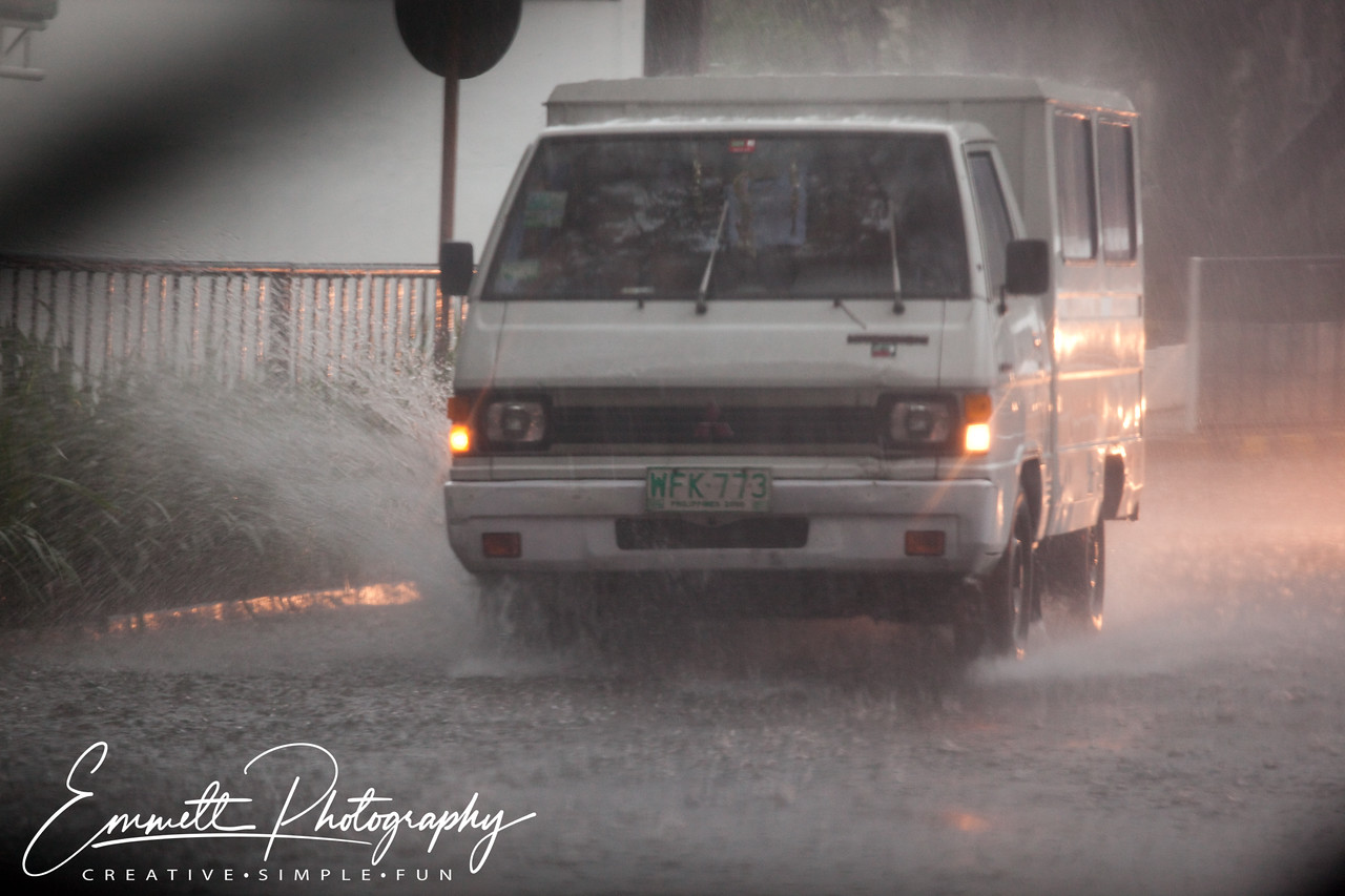 The rain has just begun but the water quickly starts to rise on McKinnley Street near EDSA, Makati, Philippines.