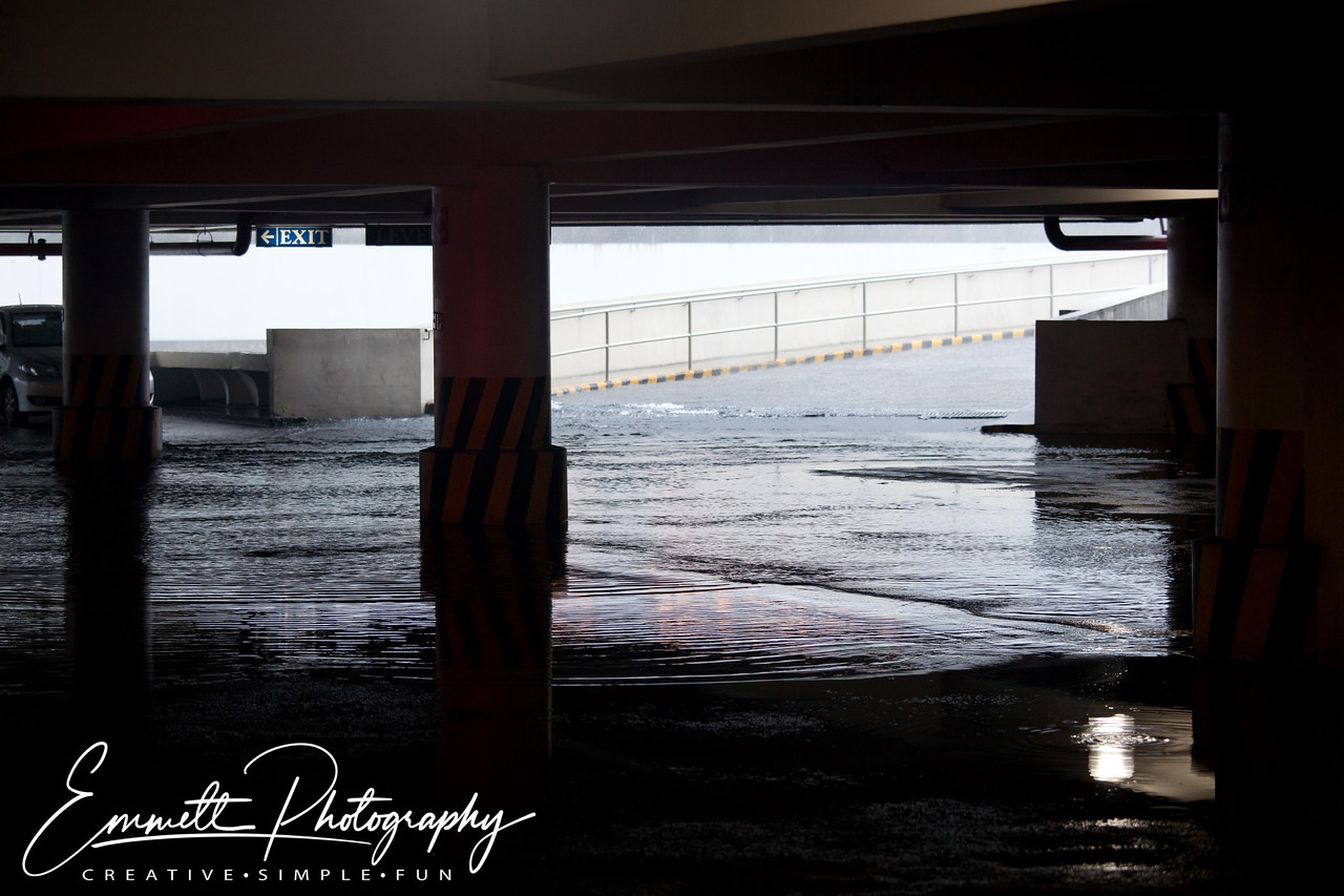 Water surges down the ramp on the 4th floor of the car park in Park Square One, Makati, Philippines.