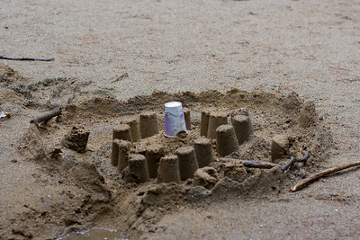 An elaborate sand castle was constructed by some kids.  It got even more elaborate later...