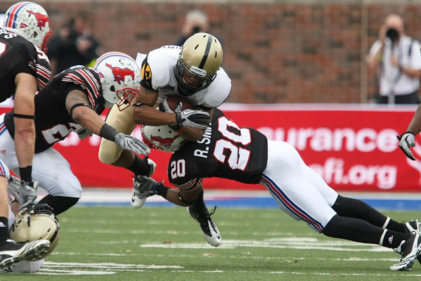 Dec 30, 2010; Dallas, TX, USA; Army Black Knights split back Malcolm Brown (middle) is tackled by SMU Mustangs defensive back Ryan Smith (20) during the second half of the 2010 Armed Forces Bowl at Gerald J. Ford Stadium.  The Black Knights defeated the Mustangs 16-14.  Mandatory Credit: Brian Utesch-US PRESSWIRE