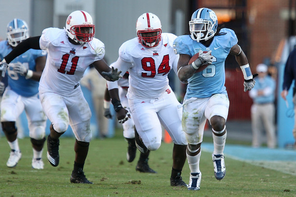 Nov 20, 2010; Chapel Hill, NC, USA; North Carolina Tar Heels running back Anthony Elzy (6) runs the ball while being pursued by North Carolina State Wolfpack defensive end Audi Augustin (11) and defensive end Michael Lemon (94) during the second half at Kenan Stadium.  The Wolfpack defeated the Tar Heels 29-25.  Mandatory Credit: Brian Utesch-US PRESSWIRE