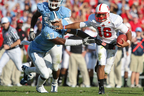 Nov 20, 2010; Chapel Hill, NC, USA; North Carolina State Wolfpack quarterback Russell Wilson (16) avoids the tackle by North Carolina Tar Heels linebacker Zach Brown (47) during the second half at Kenan Stadium.  The Wolfpack defeated the Tar Heels 29-25.  Mandatory Credit: Brian Utesch-US PRESSWIRE